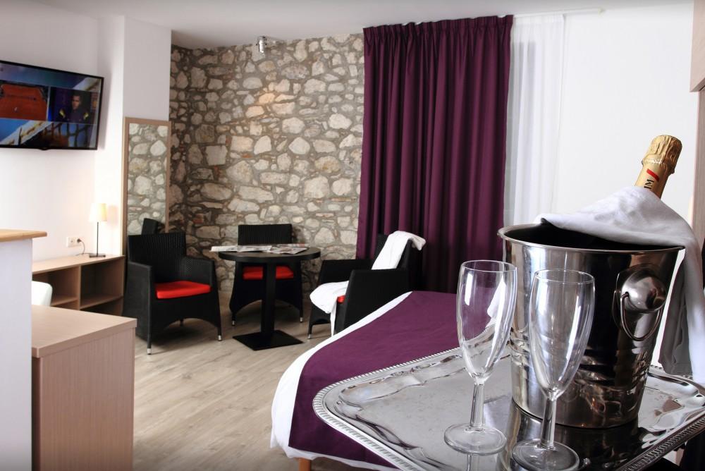 Photo de la chambre de luxe de l'Hôtel Terranostra, avec bouteille et coupes de champagne